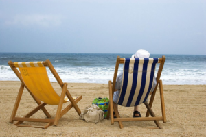 Image of two beach loungers one occupied by a person wearing a hat.
